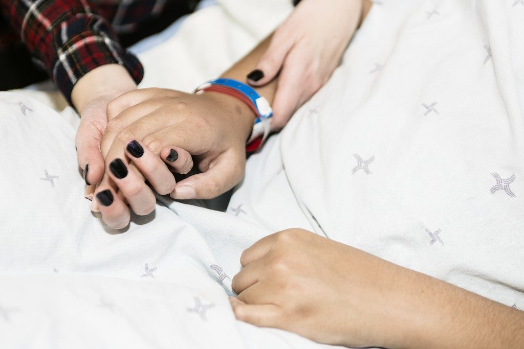 Holding hands of a patient and loved one