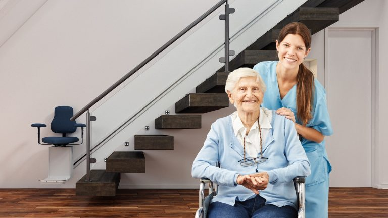 Senior and caretaker posing with stair lift behind