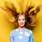 Woman with healthy hair in yellow background