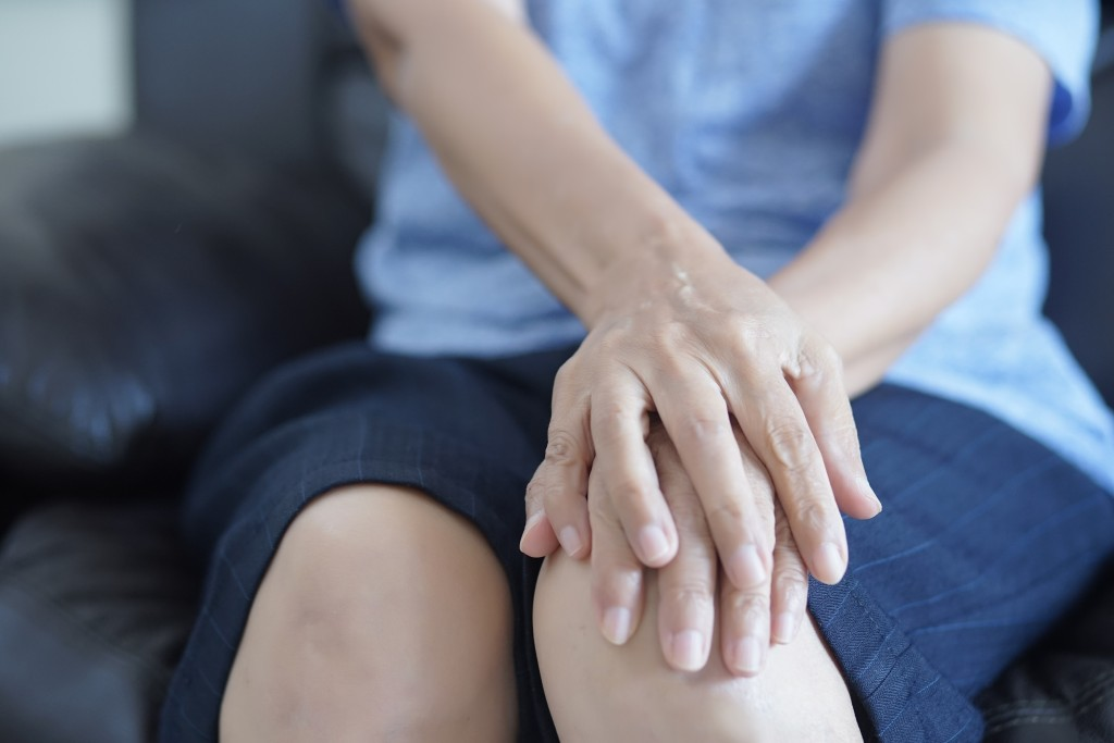 Elderly woman holding on to her knee