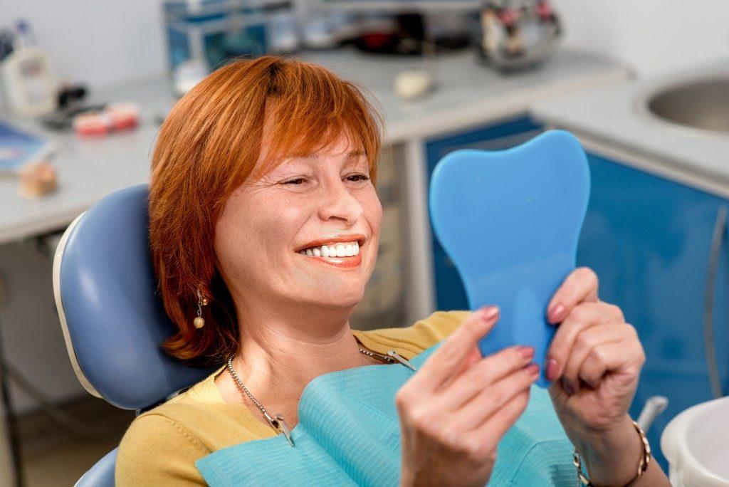 Woman checking teeth on the mirror