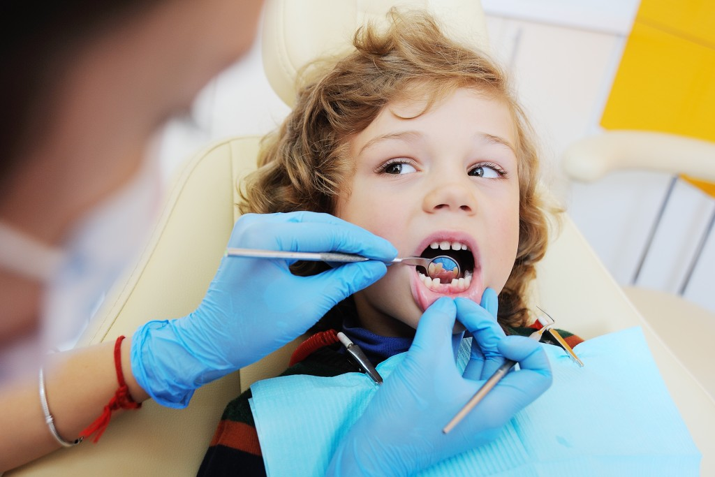 dentist checking cavities on a child's teeth