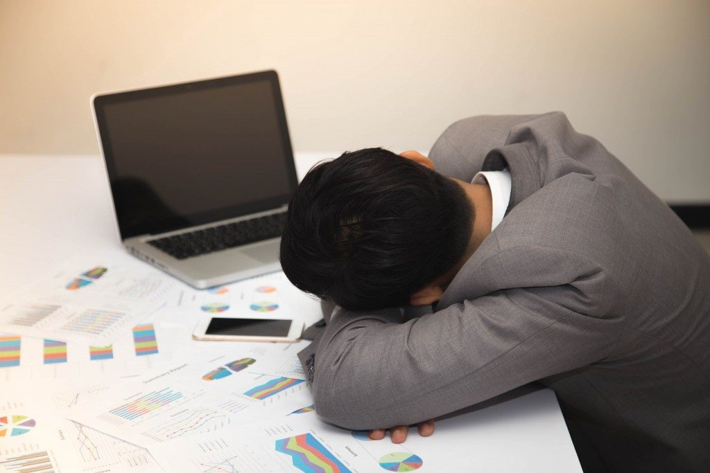 fatigued businessman asleep on his desk