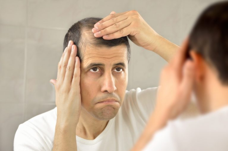 Man checking hair at the mirror