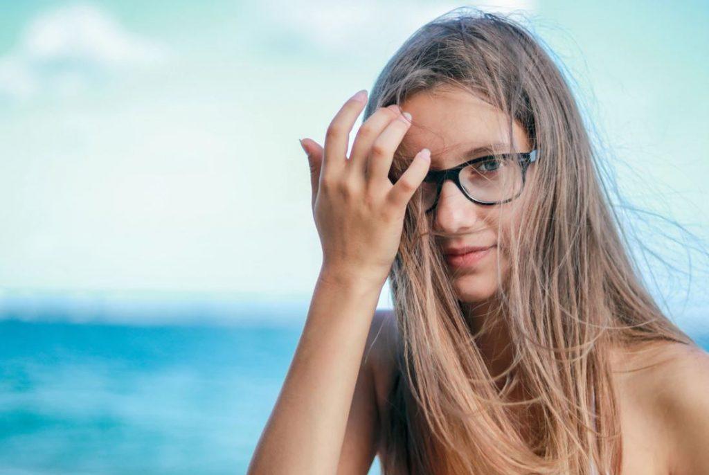 woman wearing black framed eyeglasses in white top