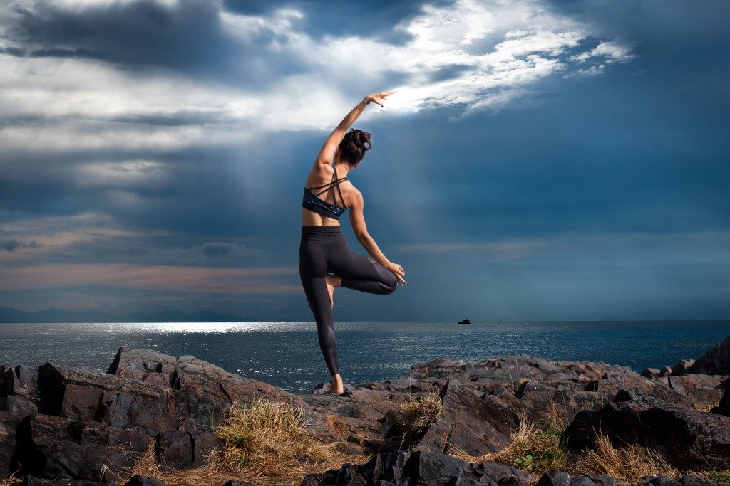 Woman doing yoga on a hill
