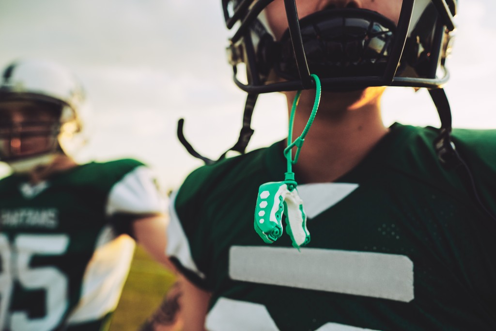 American football player with his mouthguard hanging