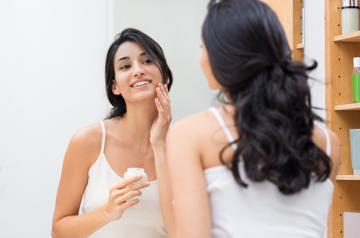 girl apllying cream on her face